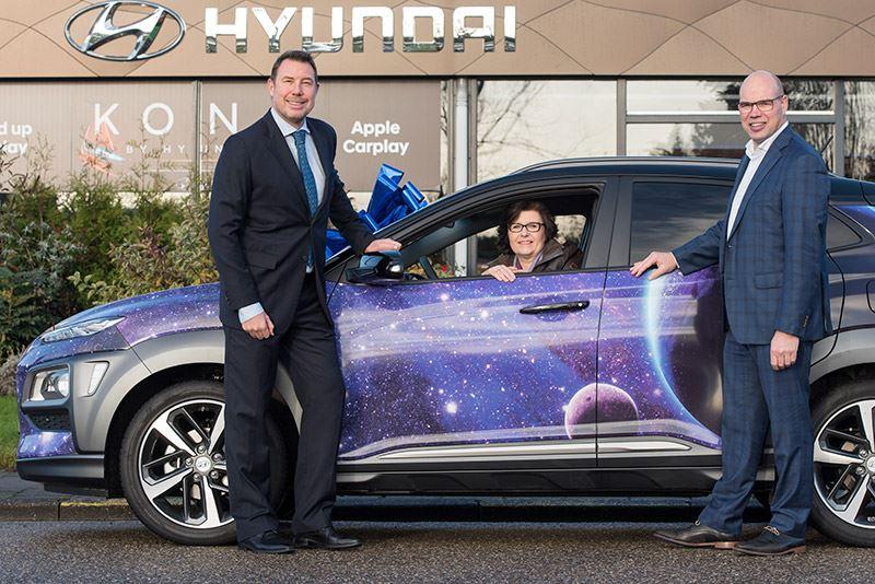 Jolanda van Orden de Graaf trots achter het stuur van haar Hyundai KONA, geflankeerd door Mike Belinfante van Hyundai Nederland (links) en Rob Knop van de Van der Linden Groep Waddinxveen.