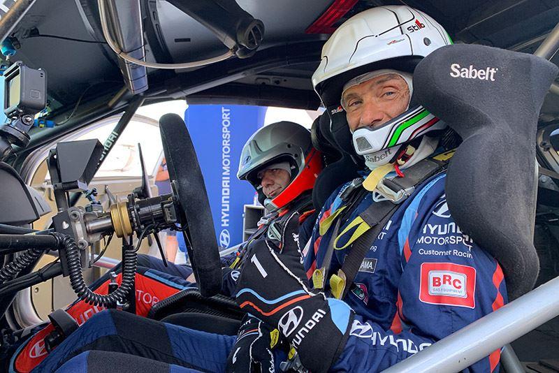 Gabriele Tarquini op de passagiersstoel naast Andreas Mikkelsen, achter het stuur van een rallyauto Hyundai i20 WRC.