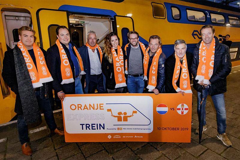 Aan boord van de Oranje Express werden de supporters getrakteerd door een voorbeschouwing van cabaretier Viggo Waas (tweede van rechts). Foto: KNVB Media