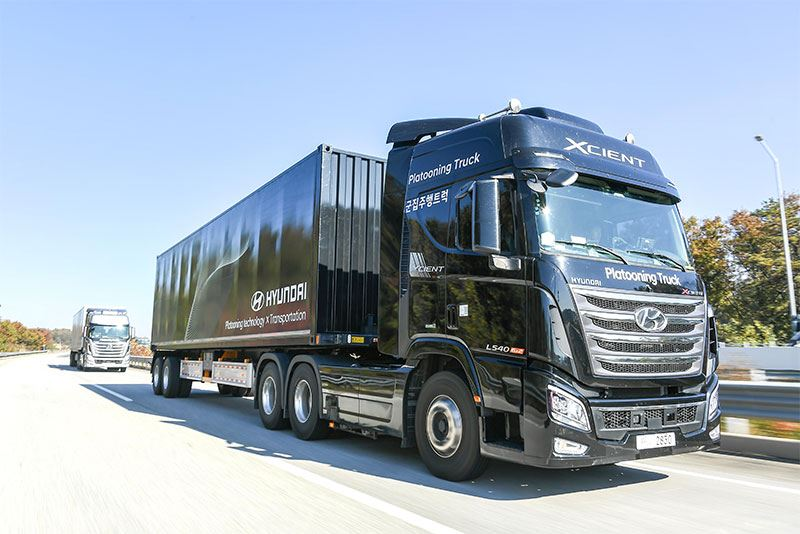 Vrachtwagens zoals de Hyundai Xcient die dicht op elkaar rijden ondervinden minder luchtweerstand: dat scheelt brandstof en zorgt voor minder emissies.