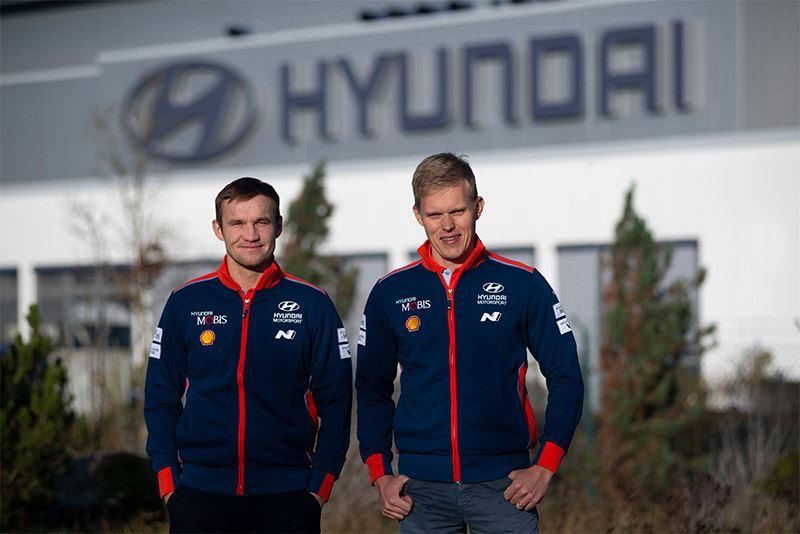 Ott Tänak (rechts) en Martin Järveoja voor het hoofdkantoor van Hyundai Motorsport in Alzenau.