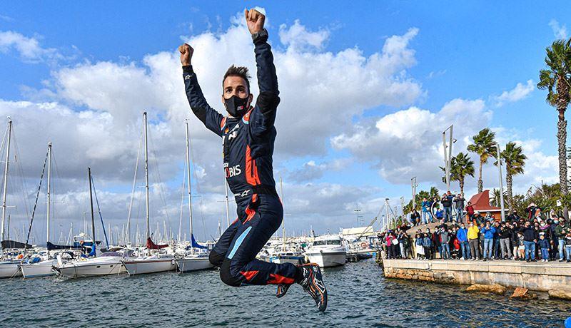 Hyundai-coureur Dani Sordo viert zijn overwinning in de Rally van Sardinië 2020 met een duik in het water.